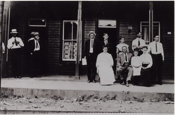 Portrait of group in front of the hotel. Later became the Clifton Hotel.