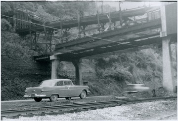 Cars pass underneath the coal conveyor in this portrait taken from the railroad tracks.