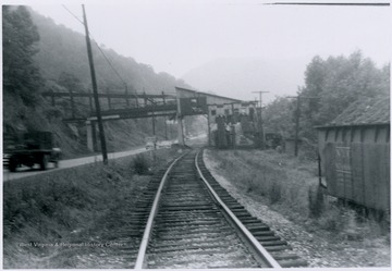 Portrait taken from the railroad tracks next to the highway. Cars and trucks can be seen passing underneath the conveyor.