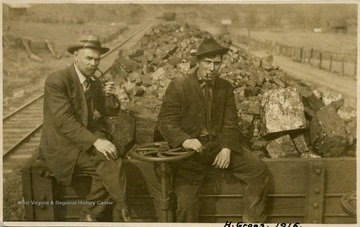Men are sitting on the front of a coal car. Both men are wearing hats and smoking pipes. The man on the right is identified as Mr. H. Groos.