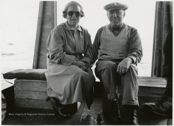 In this portrait, Menk and an unidentified woman are sitting together. Menk has on a hat and the woman is wearing sunglasses.