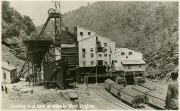 "On the front: ""Loading coal cars at mine in West Virginia."""