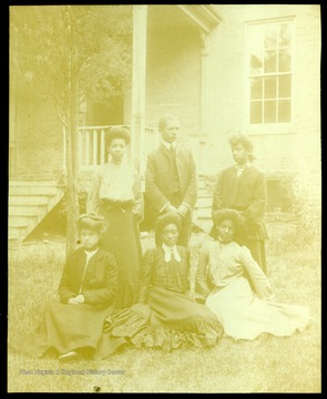 Six students of the Storer College class of 1904 on the campus lawn in front of a building.
