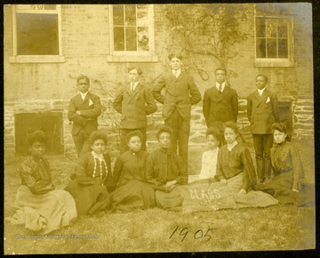 "Twelve students on the lawn of Storer College with two women holding a ""Class of 1905"" banner."