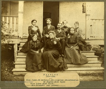 Faculty of Storer College, 1899-1901, sitting on the front steps of a building. First Row: Miss James, Mr. McDonald, Mrs. Lightner, Miss Johnson. Second Row: Mr. Hughey, Miss Sands. Third Row: Miss Baker, Miss Smith. Not Present: Mrs. Brackett