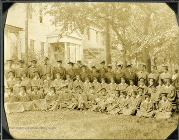 Class of 1927 sitting on lawn of Storer College in caps and gowns.