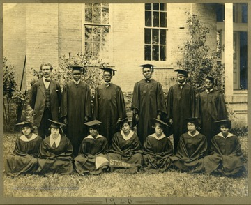 Class of 1920 in caps and gowns near a building at Storer College. First Row: Pres. McDonald, Harris, Clark, Lee, Walker, Redman. Second Row: Paker, Freeman, Arrington, Snowden, Harmon, Scott, Wildy.
