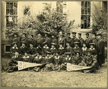 'The Famous Class' Class of 1921 graduates in caps and gowns. First Row: Barnum, A. Taper, Law (Polland), Hopewell, Arnett, Pres. McDonald., Jackson, Hill, C. Taper, Howard, C. Johnson, Morton. Second Row: Green, Williams, Jackson, Holley, Roper, Calloway, Roas, Cambell, Napper, Chandler, Lee. Third Row: E.D. Johnson, McDaniel, F. Johnson, Thornton, Shelton, Blake, Paskle, White.