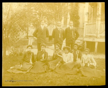 Nine Storer College graduates, class of 1902, sitting and standing on lawn of campus.