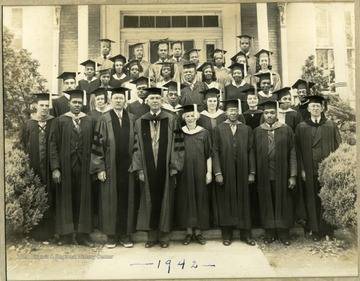 Group photo of Storer College, class of 1942, standing in caps and gowns on front steps of building on campus. Pres. and Mrs. McDonald in middle of bottom row.