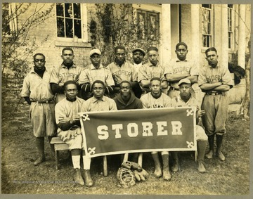 "Storer College baseball team in uniform in front of building. Front row holding ""STORER"" banner."
