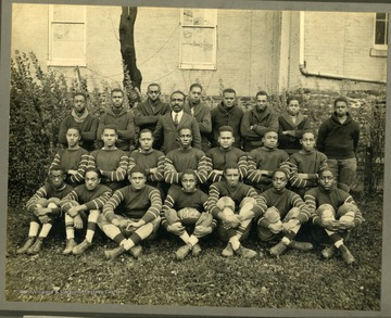 Storer College Football team in uniform by building. Back Row: Mantley, Bentley, C. Hopewell, Pierce, Smith, E. Brooks, Glover, C. Brooks. Prf. Drew, Coach. Middle Row: Briscoe, Bruner, Willims, Gaiters (Captain), Fraxier, Taylor, Mitchell. Front Row: Brown, Cannady, Lee, Toodle, Tainey, Ellison, Hill.