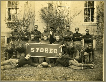 Storer College Football team in uniform near building.