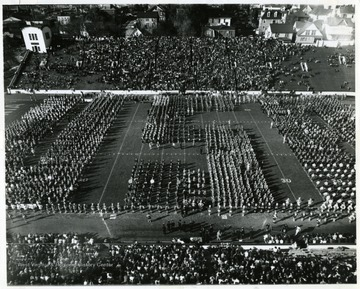 "Band Day halftime field show at the WVU-Kentucky game. ""Forty four high school bands from West Virginia and nearby Pennsylvania, some 3000 bandsmen came together on Mountaineer Field for the 1964 Band Day Show."""