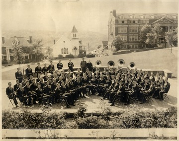 WVU Marching Band sitting in front of Wise Library. The Lutheran Church and Colson Hall are visible in the background.