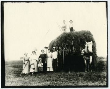 On the load, Nellie Schroth Aegerter, Louis Haslebacher. Standing left to right, Frieda Aegerter Stadler, unknown, Olga Aegerter Holtkamp, Lena Haslebacher Burky, Paul Aegerter, unknown. Children unknown.