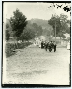 Several men and women, marching down a dirt road, many playing instruments.