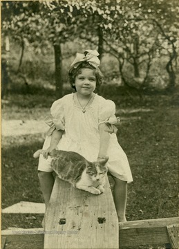 Frances D. Packette and her pet cat, Schley-Puss, on a see-saw.