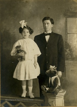 The young girl holding a teddy bear is Frances Davenport Packette. The older boy is possible her brother, Willie.