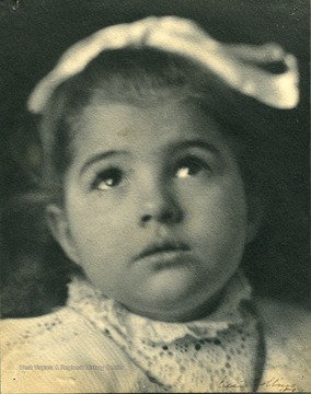 Young girl, possibly Frances Davenport Packette, gazing up, wearing a hair ribbon and lace collar.