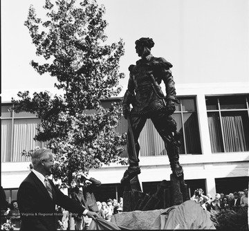 West Virginia Governor Arch Moore pulls away the covering on the Mountaineer Statue outside the Mountainlair on the West Virginia University campus.