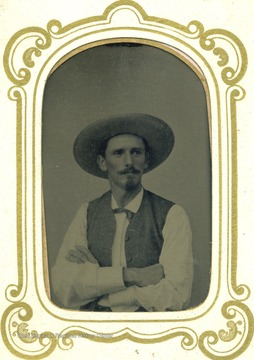 Unidentified man wearing a large hat, vest, goatee and mustache. The tintype is encased in a small glass frame.