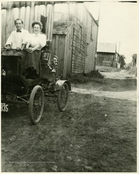 Young man and woman ride in a Model T automobile down a dirt road.