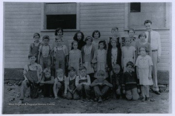 A group of Fletcher School students stand in front of the school house with their teacher, Joseph Lyons.