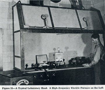 Unidentified man stands next to lab hood.