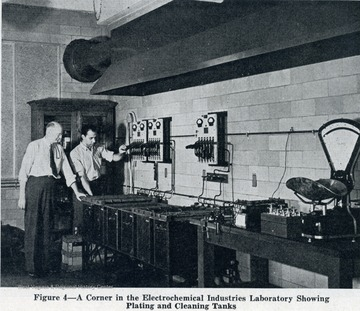 Two unidentified researchers working at the plating and cleaning tanks in the lab.