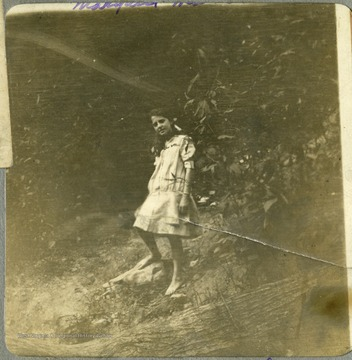 Barefoot little girl, Margaret Mathers standing in a wooded area.