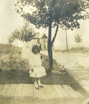 Little Margaret Mathers, daughter of Max and Anna Mathers, posing on the boardwalk at her home.