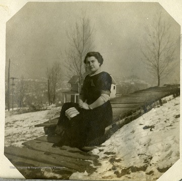 Anna Mathers poses on the boardwalk outside her house, surrounded by snow covered ground.