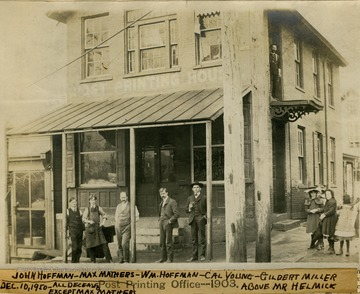 Standing in front of shop, left to right: John Hoffman, Max Mathers, William Hoffman, Cal Young, and Gilbert Miller. Standing outside a second story door is Mr. Helmick. The little girls are not identified.