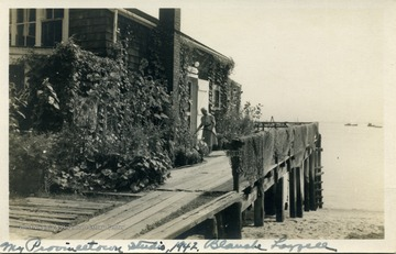 Post card photograph of artist Blanche Lazzell watering her flowers in front of her studio which is on a pier in Provincetown, Massachusetts located on Cape Cod.