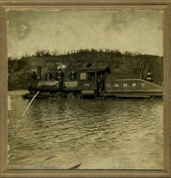 Fred Secrest, an engineer for the Kanawha and Michigan Railway was not to be stopped by the flooded Wagner Railroad Yard in Point Pleasant, along the Ohio River. He backed the engine into the flooded yard, pulled down the hose into the water and filled up the boiler. Secrest is seen standing in back of the locomotive. (Engine 51-2511-566; Bald. 0-6-0 '87)
