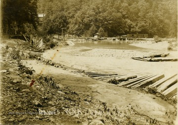 "Postcard photograph of the flood damage along Cabin Creek including the railroad tracks in the background. Information on the back: ""Hinton Daily News Collection - John Faulkner Collection From Jim Pettrey to Stephen Trail 1997""."