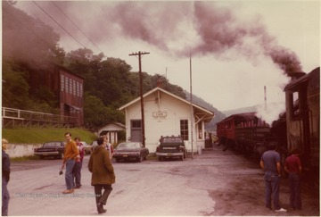 "Color photograph of Depot, surrounding buildings and train with steam raised, on the track. Information on the back: ""Stephen Trail Collection, Cass, Pocahontas Co. , WV; from Buddy Strokes 3/2000; Photographer Dr. J. W. Strokes, M. D.""."