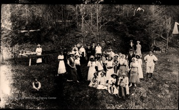 "A group of casually posed people in a wooded area, two holding Concord College banners. Other information includes ""HDN Coll. early 20th Century, S. Trail 2002""."
