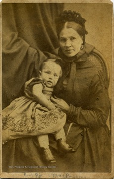 A carte de visite photograph of a woman holding a small child. There is a federal revenue stamp on the back of the photograph, indicating a tax had been paid on the image. This stamp tax was passed by Congress to pay for raising costs of the Civil War from 1864 to 1866.