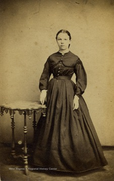 "A carte de visite of a young woman wearing Civil War period fashion and hair style. There is also a revenue stamp on the back of the photograph with the date ""July 24, 1866""."
