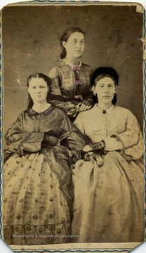 A carte de visite of three unidentified women dressed in Civil War era fashion and hair style.