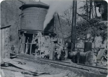 "The man standing beside the steam boiler is J. A. Coulter, who later became an engineer for C&O, others in the photograph are not identified. The water tank is the original, it was replaced several years later by another. This photograph was taken before the double track was made through Sewell. Other information on the back of the photograph includes: "" C to Ry Engineer deceased via Jim Henry Waverly - C. A. Coulter 209 First Street, West Logan, W. Va. 25601""."