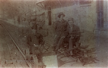 "Three unidentified men seated on a velocipede at the Chesapeake & Ohio (C&O) Depot and Telegraph Office in Prince, West Virginia. ""J. S. Sampson Collection"""