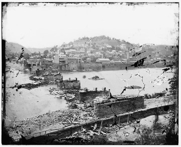 "The first of nine times this bridge, which crossed the Potomac River into Maryland, was destroyed during the Civil War. The damage in the photograph was the work of Confederate Colonel Thomas (later General ""Stonewall"") Jackson's troops, before pulling back to Winchester in June, 1861. The shells of the burned Armory buildings still stands in the background below the town."