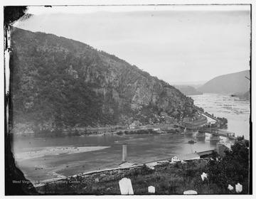 Maryland, the Chesapeake & Ohio Canal and a reconstructed Baltimore and Ohio Railroad bridge on the Potomac River as viewed from the Harpers Ferry cemetery. Note the head stones in the foreground and the smoke stack of the burned out United States Armory below. The photograph was taken during the Civil War.