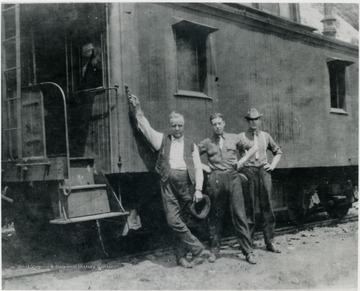 "Ro Murrell, center, stands in front of caboose with two unidentified crew members. Inscription on the back includes: ""...from Ro Murrell Collection..."""