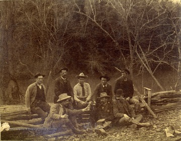 Unidentified engineers, working on the Ohio extension in Southern West Virginia, two men, sitting in the middle, are holding revolvers.