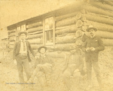 Unidentified engineers, working on the Ohio Extension, pose in front of a log cabin.