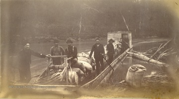 A barge loaded with supplies for the engineers and crews working on the Ohio Extension along the Tug Fork and Big Sandy Rivers between Welch in McDowell County and Kenova in Wayne County. None of the men are identified in the photograph.